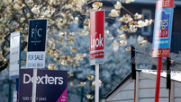 Estate agents' For Sale and To Let signs stand on display outside residential properties in London.
