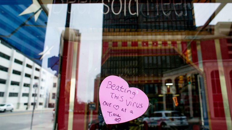 """A hand made sign placed on the window of a restaurant reads """"Beating This Virus One Heart at a Time"""" in Detroit."""