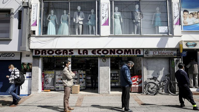 Men wearing protective masks stand in line, while practicing social distancing, outside a pharmacy in Bogota, Colombia.
