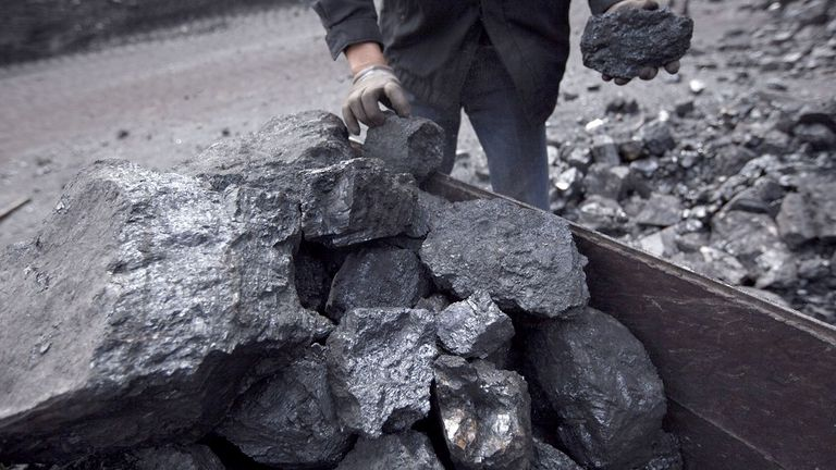 A miner holds chunks of coal from a pile