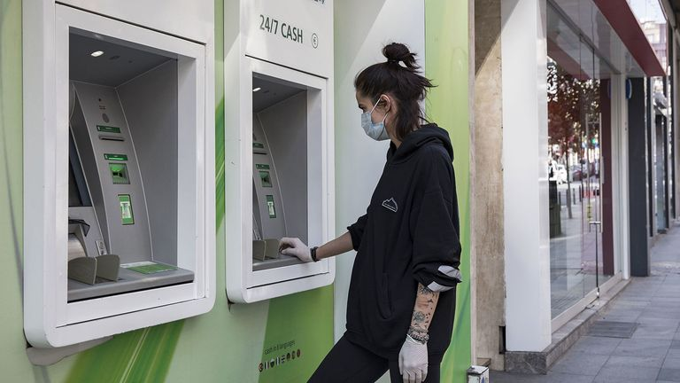 A customer wearing a protective face mask and surgical gloves uses an ATM in the Nisantasi district in Istanbul, Turkey.