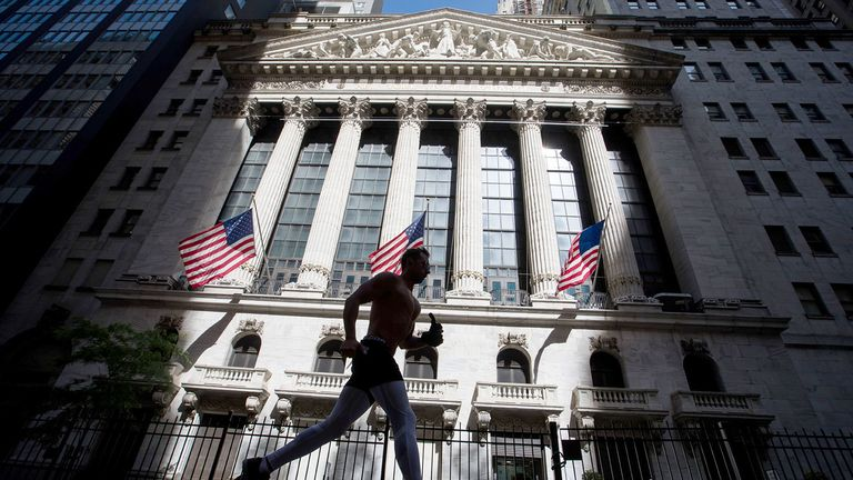 A jogger passes in front of the New York Stock Exchange on June 17, 2020