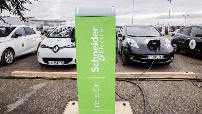 Electric vehicles connected to a charging station manufactured by Schneider Electric.