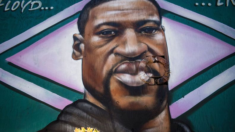 Fresh flowers are arranged in front of a mural depicting George Floyd in Oakland, Calif., on June 3, 2020.