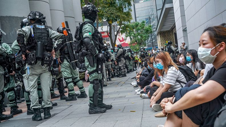 Demonstrators detained by riot police sit in front of a shopping mall in the Causeway Bay district during a protest in Hong Kong.