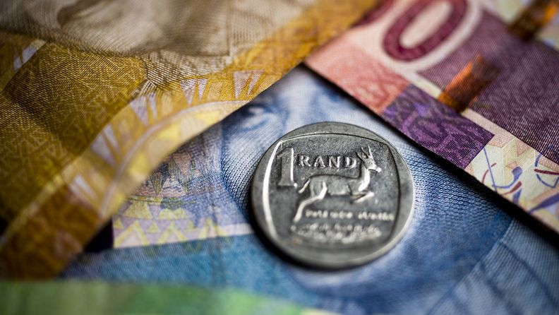 A South African one rand coin sits on South African rand banknotes